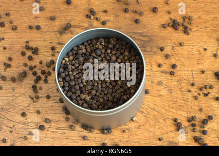 Still life with black peppercorn inside round silver jar and scattered on vintage wooden background. Horizontal photo closeup - Stock Photo