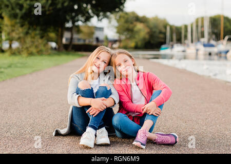 Portrait of two smiling girls sitting head to head on the ground - Stock Photo