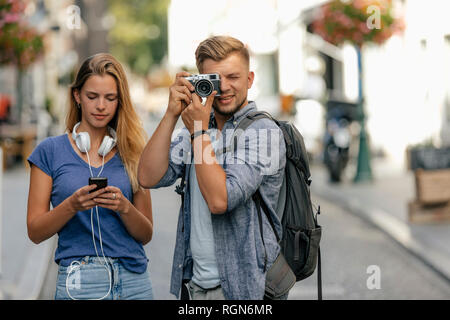 Netherlands, Maastricht, young couple exploring the city taking pictures - Stock Photo