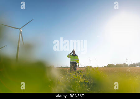 Engineer standing in a field at a wind farm talking on cell phone - Stock Photo