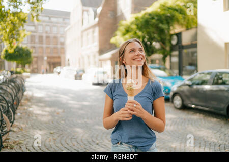 Netherlands, Maastricht, smiling blond young woman holding ice cream cone in the city - Stock Photo