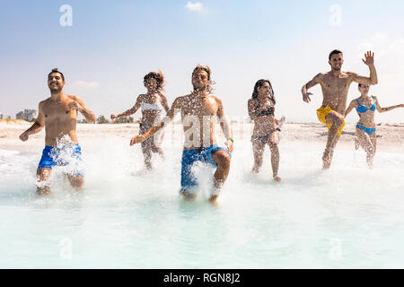 Group of friends having fun on the beach, running into the water - Stock Photo