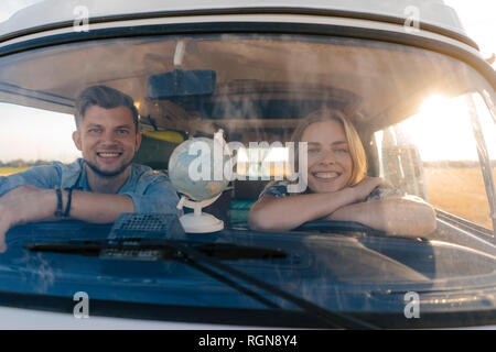 Portrait of happy young couple on a trip in camper van - Stock Photo