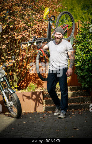 Portrait of man switching from motorbike to bicycle - Stock Photo