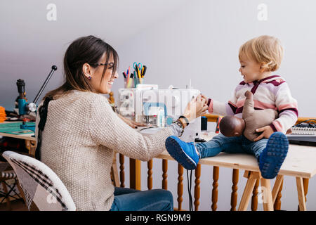 Happy mother with little daughter at home using sewing machine - Stock Photo