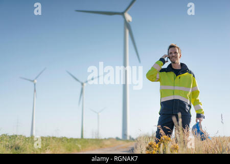 Smiling engineer standing in a field at a wind farm talking on cell phone - Stock Photo