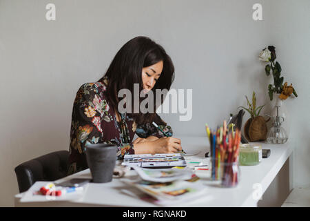 Illustrator drawing at work desk in an atelier - Stock Photo