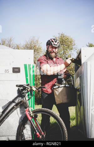 Portrait of man recycling glass bottle in bottle cyclist