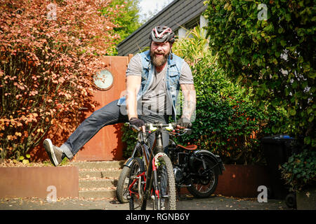 Portrait of happy man switching from motorbike to bicycle - Stock Photo