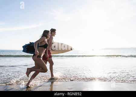 France, Brittany, young couple with surfboard running in the sea