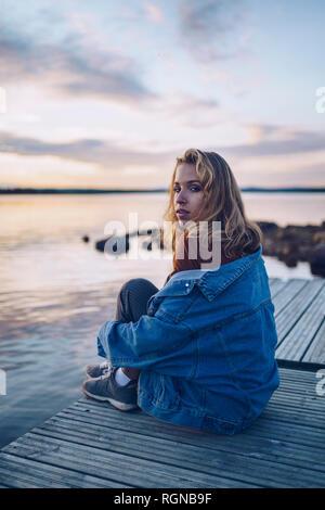 Young woman sitting at lake Inari, looking at camera, Finland