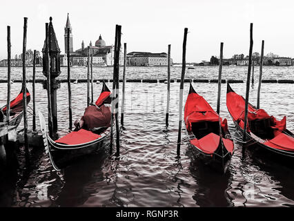 Red vintage gondolas docked at the pier the Piazza San Marco in Venice, Italy. Color in black and white - Stock Photo