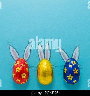Three chocolate eggs in colorful aluminium foil with painted easter bunny ears on blue background - Stock Photo