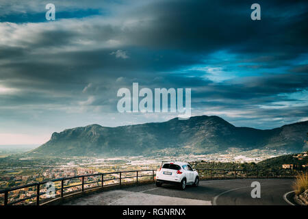 Terracina, Italy - October 15, 2018: White Color Car Nissan Juke Pre-facelift Parked On Road On Background Beautiful Landscape With Mountains In Italy - Stock Photo