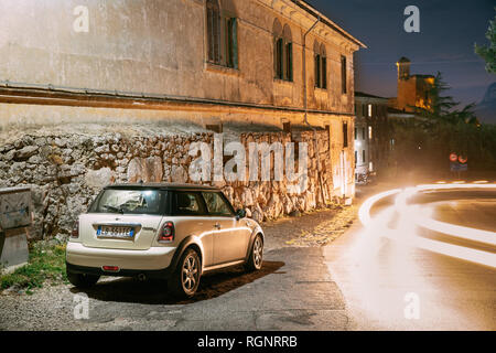 Terracina, Italy - October 15, 2018: White Color Hatch Pre-facelift Mini Cooper R56 Car Parked On Background Castle Castello Frangipane In Evening Nig - Stock Photo