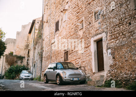 Terracina, Italy - October 15, 2018: Front View Of Gray Color 2004 Mini One Hatch (pre-facelift model) Mini Cooper Car Parking On Street Near Old Ital - Stock Photo