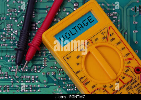 Digital multimeter multitester on a circuit board with the word voltage on the display - Stock Photo