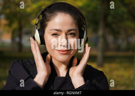 young woman in her 20s listening to music with cordless over-ear headphones outside in nature on a sunny day - Stock Photo