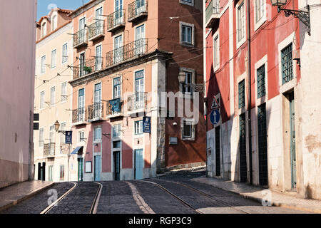 Tram tracks in a hilly street in Lisbon with red houses in sun. - Stock Photo