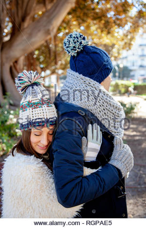 Young woman dressed in winter gloves and woolen hat hugs in love and with eyes closed to her boyfriend from behind - Stock Photo