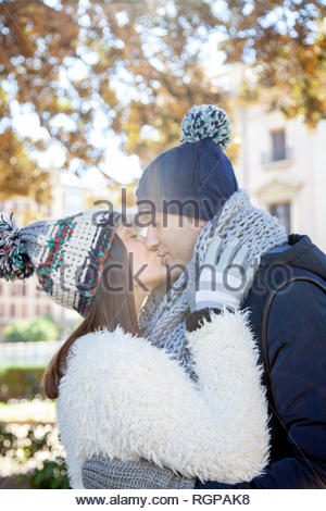 Young couple dressed in winter clothes and wool hats kiss passionately in a public park - Stock Photo