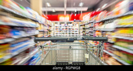 An empty shopping cart between shelf rows in the supermarket with motion blur. - Stock Photo
