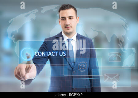 Man touching contact us button using index finger on transparent display with phone and email symbols on world map background - Stock Photo
