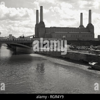 1950s, historical, view of Battersea Power Station at Nine Elms, Battersea on the South bank of the River Thames, London, England, The coal-fired power station was in fact two power stations in a single building, Battersea A was constructed in the 1930s and Battersea B between 1953-1955, with both being built to a nearly identical design, providing the iconic four-chimney structure seen in the picture. Created by the famous architect, Sir Giles Gilbert Scott, construction started in 1929 and it became one of the largest brick buildings in the world. It was finally decommissioned in 1983. - Stock Photo