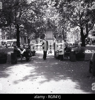 1960s, Summer time and people sitting on benches in the small public park or garden area at Leicester Square, in the West End of London, England, UK. The statue of the English paywright, William Shakespeare by Giovanni Fontana can be seen in the picture, a  sculpture in the centre of Leicester Square Gardens since 1874, a result of improvements made by Albert Grant who brought the square in that same year. - Stock Photo