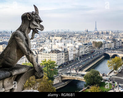 One of the most famous chimera statues of Notre-Dame de Paris cathedral, gazing at the city from the towers gallery. - Stock Photo