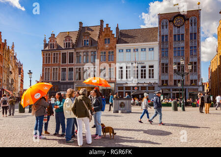 25 September 2018: Bruges, Belgium - Tour group under orange umbrellas in the centre of the city, Markt Square, on a sunny, autumn day with glorious b - Stock Photo