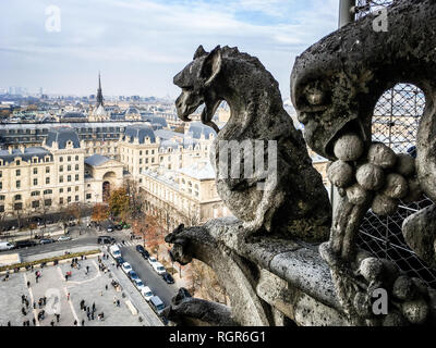 Two of the famous chimera statues of Notre-Dame de Paris cathedral, gazing at the city from the towers gallery. - Stock Photo