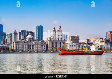 1 December 2018: Shanghai, China - Cargo ship on the Huangpu River passing The Bund, the historic business area of Shanghai. - Stock Photo