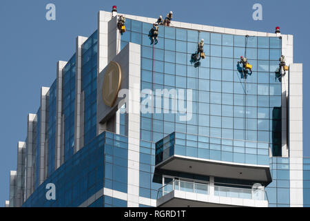 DUBAI, UAE - February 15, 2018: Men clean up the facade of the modern skyscraper in Dubai, United Arab Emirates - Stock Photo