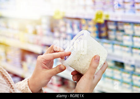 Buyer hands with plastic container of cottage cheese in the grocery store - Stock Photo