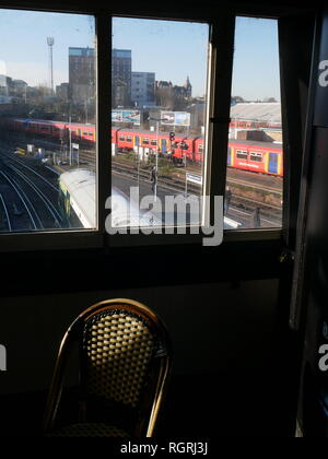 A view through a window of a train pulling in to the platform at Clapham Junction railway station in South London. - Stock Photo