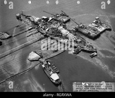 Salvage operations, USS Oklahoma (BB-37), sunk during the Pearl Harbor attack. Aerial view from the starboard bow, with the ship in the 2°-10° position during righting operations. - Stock Photo