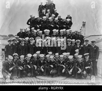 19 black and white photos from the service of Francis Philip Goodwin during World War II, donated by his family. Focus is U.S. Navy submarines and submarine life. Shown are the launching of USS Sea Dog (SS-401) as well as her commissioning crew and a party celebrating the event. Launching photo is alternately labeled USS Segundo (SS-398), leading to some confusion on identification. Photos of sailors on deck of USS Pilotfish (SS-386) alongside USS Proteus (AS-19) at Yokusuka. Deck guns can be seen, as well as the boat's dog mascot. - Stock Photo