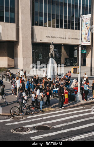 New York, USA - June 01, 2018: People by the statue of Adam Clayton Powell Jr. in Harlem, NYC. Since 1920s Harlem is a major African American resident - Stock Photo