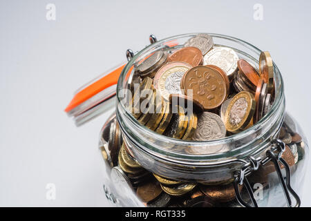 Savings UK - a glass storage jar completely full of british coins and notes, saved up.  Concept illustration for pension planning, rainy day fund, emergency money, home banking, cash in hand, accumulated wealth - Stock Photo