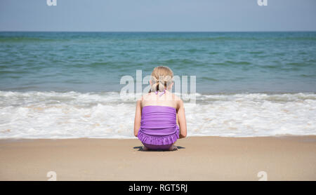 A 9 year old girl crouching in front of the waves coming ashore on the beach. - Stock Photo