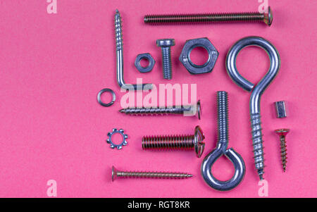 Abstract pink plastic background with screws nuts and washers. - Stock Photo