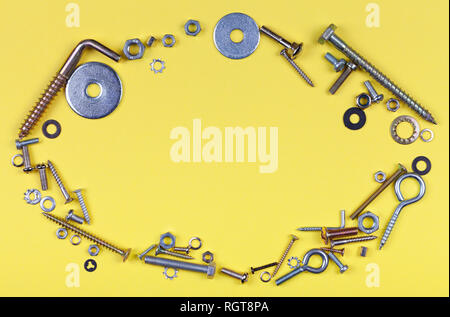 Oval frame with yellow background with screws nuts and washers. - Stock Photo