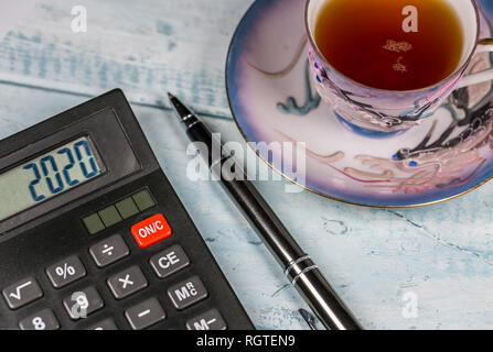Cup Of Tea, Calculator and Pen On Wooden Desk - Stock Photo