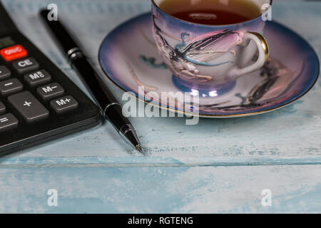 Calculator, Pen and Cup Of Tea On The Wooden Table - Stock Photo