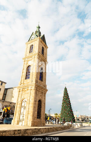 Tel Aviv - December 23, 2018: The Clock tower in Old Jaffa town centre and decorated Christmas tree  near by in Tel Aviv, Israel - Stock Photo