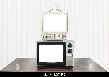 Two vintage television on old table with cut out screens. - Stock Photo