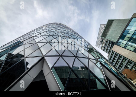 London,UK - January 26th 2019: The modern glass buildings of the Swiss Re Gherkin on July 28, 2007 in London, England. This tower is 180 meters tall a - Stock Photo