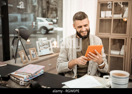 Smiling positive guy with lush beard observing information on smartphone - Stock Photo