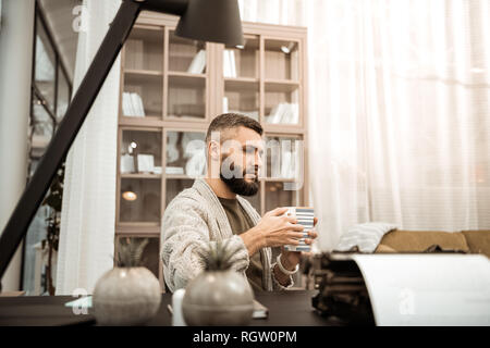 Serious thoughtful man in knitted cardigan carrying big cup of tea - Stock Photo